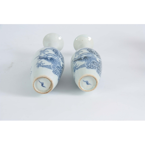 148 - A SLENDER PAIR OF SMALL 18TH / 19TH CENTURY BLUE AND WHITE VASES decorated with dragons 20cm high....