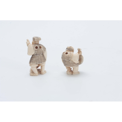 207 - A PAIR OF JAPANESE IVORY NETSUKE one modelled as a man holding his catch of fish, the other holding ...