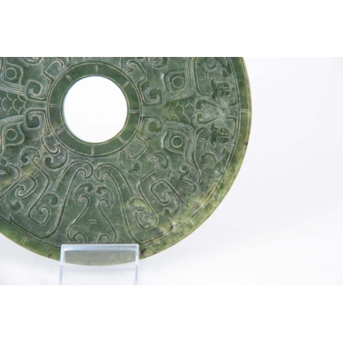 211 - A CHINESE SHALLOW CARVED SPINACH JADE PI decorated on both sides with a stylised ox and various othe...