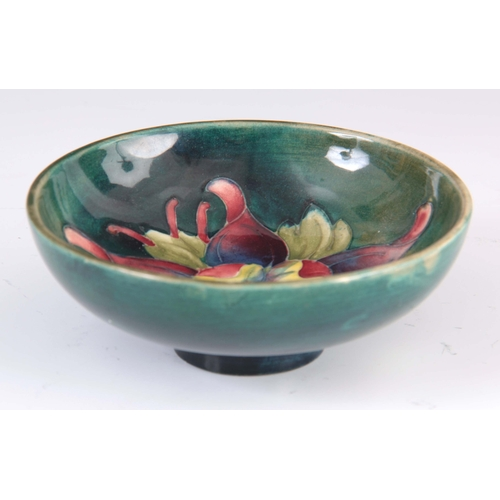 42 - A CIRCA 1950S WALTER MOORCROFT COLUMBINE PATTERN FOOTED BOWL on a green ground 4cm high, 11.5 cm dia...