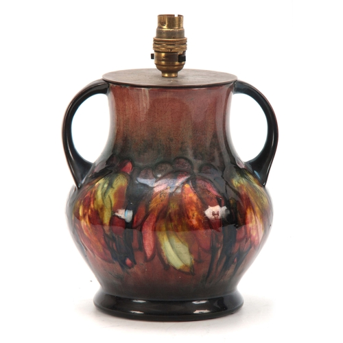 48 - A 20TH CENTURY MOORCROFT LEAVES AND BERRY PATTERN TWIN HANDLED LAMP having flambe glaze with signed ...