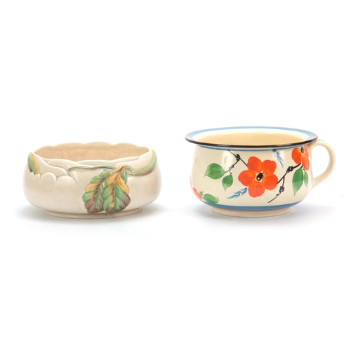 57 - TWO PIECES OF 1930'S CLARICE CLIFF POTTERY comprising a fantasque chamber pot decorated with leaves ...