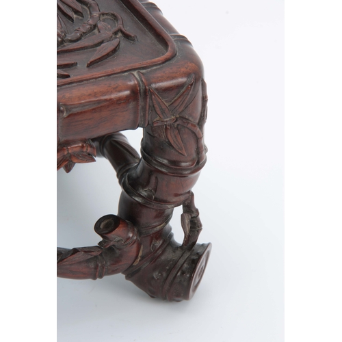282 - A SMALL CHINESE HARDWOOD STAND having carved simulated bamboo decoration with cabriole style legs un...