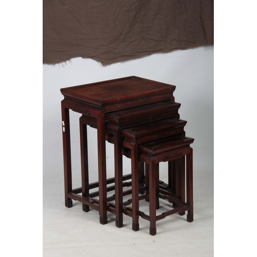 290 - A SET OF FOUR LATE 19TH CENTURY CHINESE NEST OF TABLES with panelled tops, above blind fretted shape...