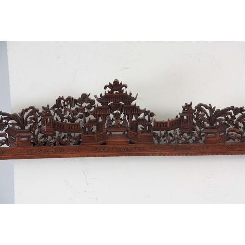 295 - A 19TH CENTURY CHINESE CARVED HARDWOOD FRAME carved with pagodas and garden scenes - 76cm high 86cm ...