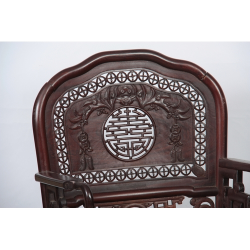 297 - A PAIR OF 20TH CENTURY CHINESE HARDWOOD ARMCHAIRS with solid shaped pierced back decorated with carv...