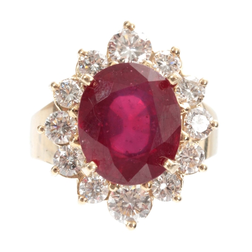 321 - A LADIES 14ct GOLD RUBY AND DIAMOND RING having a 7ct oval brilliant-cut ruby surrounded by 12 diamo...