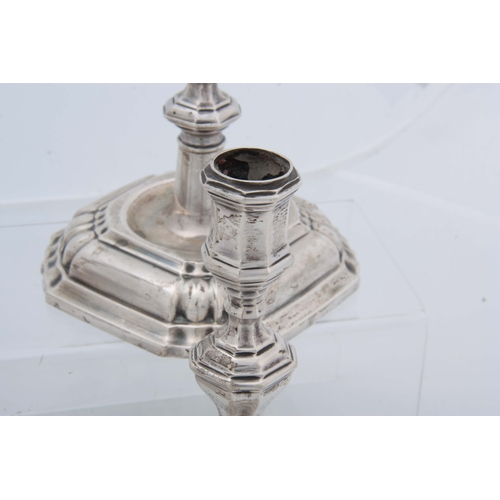 382 - A SET OF FOUR CONTINENTAL CAST SILVER CANDLE STICKS having moulded square bases, octagonal stems, ap...