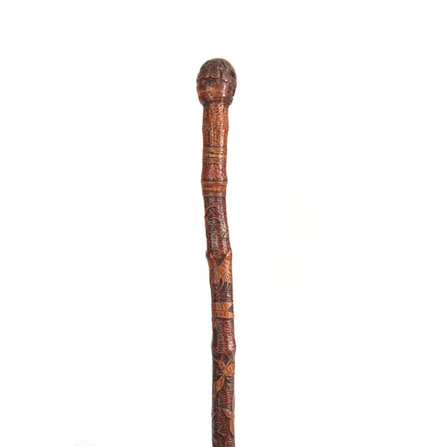 450 - A 19th CENTURY JAPANESE BAMBOO WALKING CANE having a root handle, the stick carved all over with var...