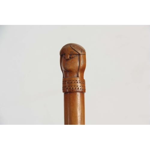469 - AN EARLY 20TH CENTURY SCANDINAVIAN HARDWOOD WALKING STICK carved with a two-faced figural handle pos...