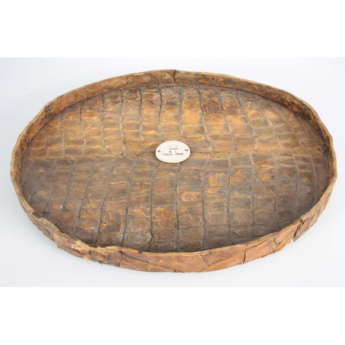 477 - AN EARLY 20th CENTURY OVAL CROCODILE SKIN SERVING TRAY BY ROWLAND WARD LTD. with presentation plaque...