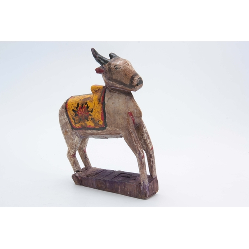 502 - A CARVED AND PAINTED HINDU NANDI COW 31cm high 20cm wide...