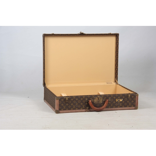 520 - A VINTAGE LOUIS VUITTON BROWN LEATHER SUITCASE with studded brass corner mounts, fasteners and lock ...