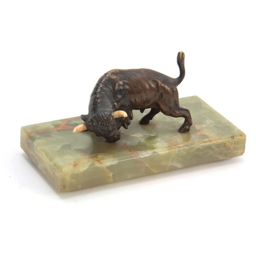 524 - AN EARLY 20th CENTURY AUSTRIAN PATINATED BRONZE SCULPTURE modelled as a bull mounted on oval onyx ba...