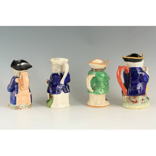 37 - A GROUP OF THREE COLOURFUL SEATED STAFFORDSHIRE TOBY JUGS each clutching a jug of ale 24cm high and ...