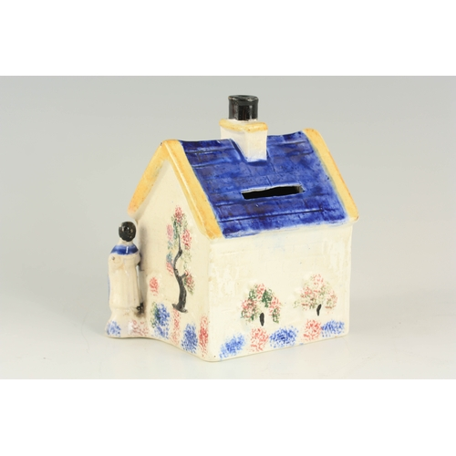 42 - A 19TH CENTURY PRATTWARE POTTERY MONEY BOX with pearlised glaze formed as a house with male and fema...