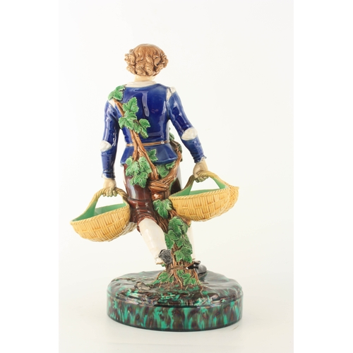 44 - A 19TH CENTURY MINTON MAJOLICA FIGURE finely modelled as a young man carrying baskets coloured in sh...