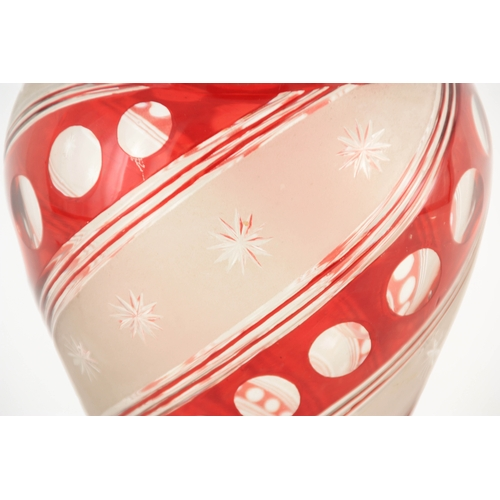 7 - A BOHEMIAN FROSTED AND RED OVERLAY BALUSTER GLASS VASE with faceted foot and neck enclosing a swirl ...