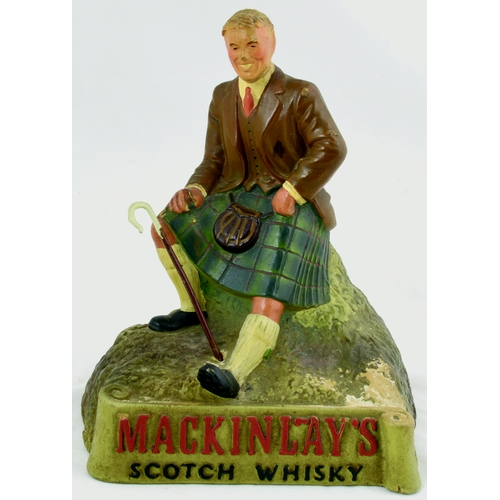 136 - MACKINLAYS SCOTCH WHISKY BACK BAR FIGURE. 7ins tall. Rubberoid kilted gent sat atop a rock MACKINLAY...