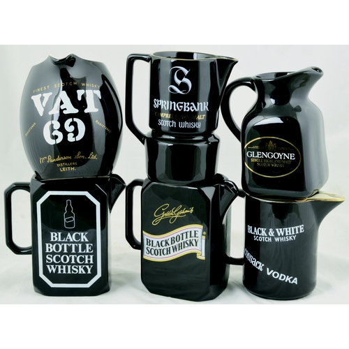 208 - WHISKY JUG GROUP. Tallest 5.5ins tall. Various shapes, makes & designs all black glaze inc. VAT 69, ...