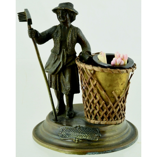 38 - METAL MATCH HOLDER. 4.25ins tall. Metal construction of lady with rake in hand, stood aside large ba...