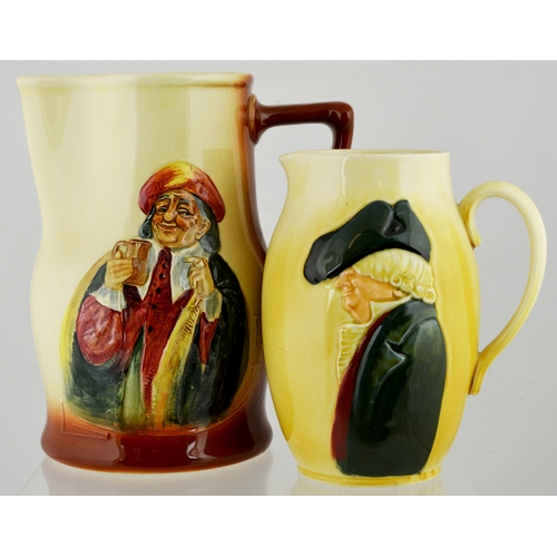 82 - QUEENSWARE JUG DUO. 8.8ins tallest, both cream bodied, one with brown handle. Each with differing sc...