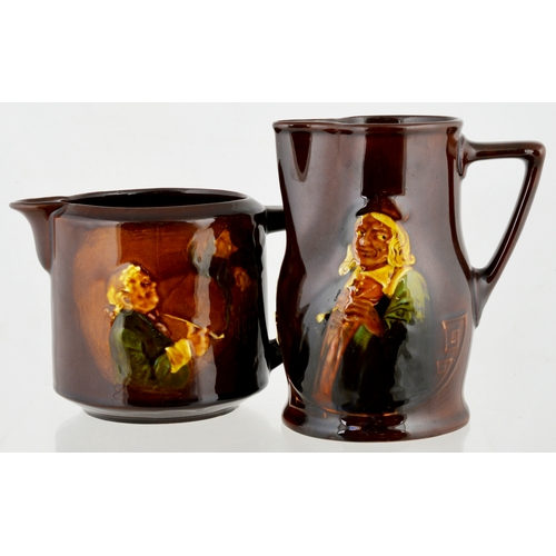 83 - KINGSWARE WATER JUG DUO. 6.1ins tallest. Both brown bodied & side handles. Different smoking images ...