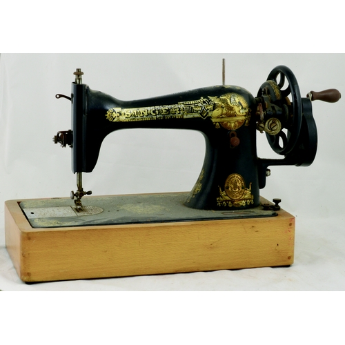 107 - SINGER SEWING MACHINE. 10.5ins tall. Cast machine, wood base & lid, gold decoration Egyptian sphinx ...