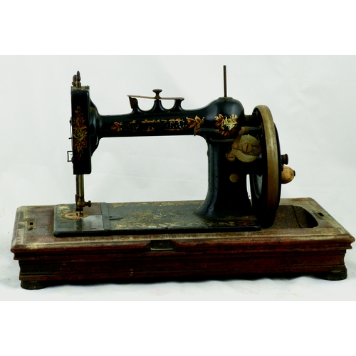 108 - HOME COMPANY SEWING MACHINE. 11.5ins tall. Cast machine, wood base, curved top, gold leaf decoration...