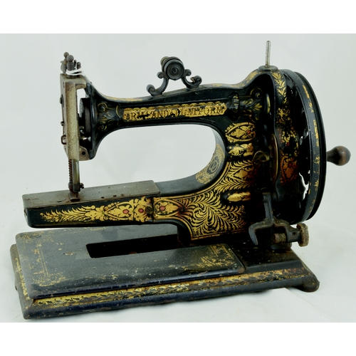 98 - E WARDS ARM & PLATFORM SEWING MACHINE. 11ins tall. Cast machine, gold decoration, hand cranked. Pate...