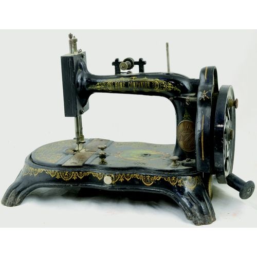 99 - HOME COMPANION SEWING MACHINE. 11ins tall. Shapely cast machine, gold decoration, hand cranked. Henr...