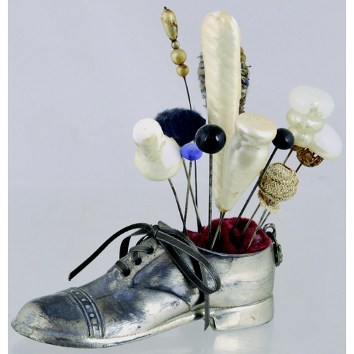 158 - SILVER METAL HAT PIN HOLDER. Formed as a shoewith a variety of hat pins. General age/ wear. (7/10)...