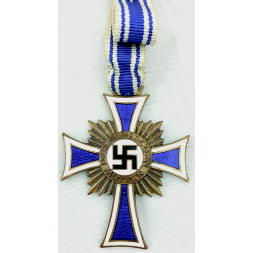 226 - HONOR CROSS OF THE GERMAN MOTHER. Gilded bronze & multicoloured enamels with period original ribbon....