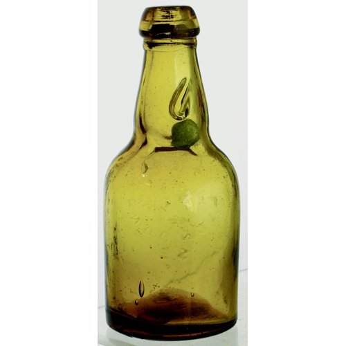 559 - DUMPY NARROW NECK CODDS PATENT 4 BOTTLE. 7.25ins tall. Amber glass, 2 neck retaining lugs, aqua marb...