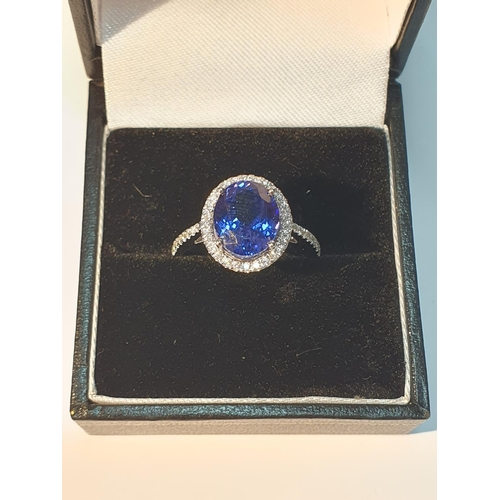 14 - An 18ct gold tanzanite and brilliant-cut diamond cluster ring. Tanzanite weight 3.56cts.Total diamon...