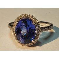 An 18ct gold tanzanite and brilliant-cut diamond cluster ring. Tanzanite weight 3.56cts.Total diamond weight 0.27ct, estimated H-I colour, VS-SI clarity. Hallmarks for Birmingham. Ring size O. 4.2gms.