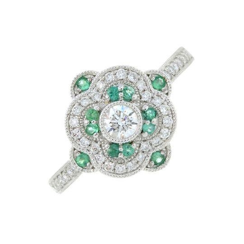 13 - An 18ct gold diamond and emerald dress ring. Total emerald weight 0.11ct. Total diamond weight 0.40c...