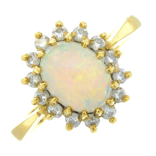 8 - An 18ct gold opal and brilliant-cut diamond cluster ring. Estimated total diamond weight 0.20ct. Hal...