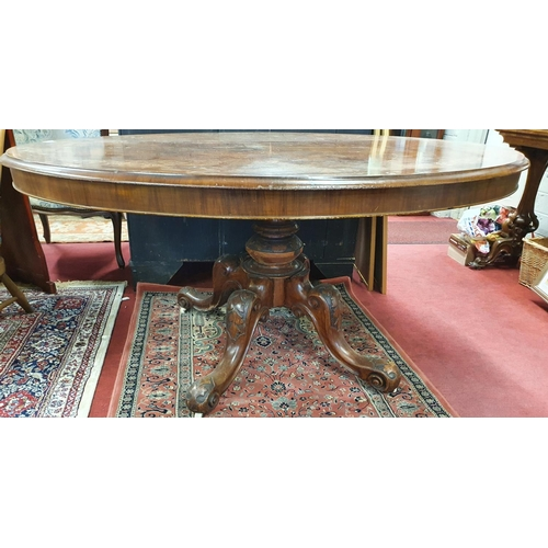 25 - A fantastic Victorian Walnut Inlaid oval Supper Table with splayed carved pod. c1860. 145 x 117 cms ...