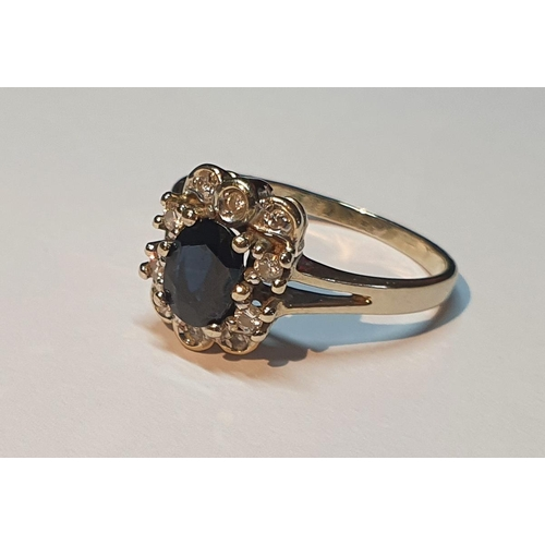 2 - A sapphire and brilliant-cut diamond cluster ring. Stamped 585. Ring size P1/2. 3.2gms.