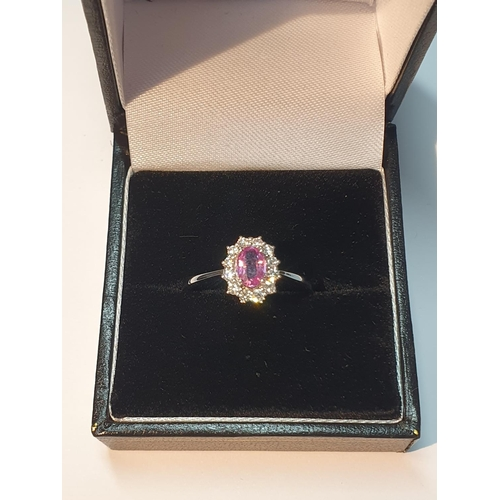 10 - An 18ct gold pink sapphire and diamond cluster ring. Pink sapphire weight 0.53ct. Total diamond weig...