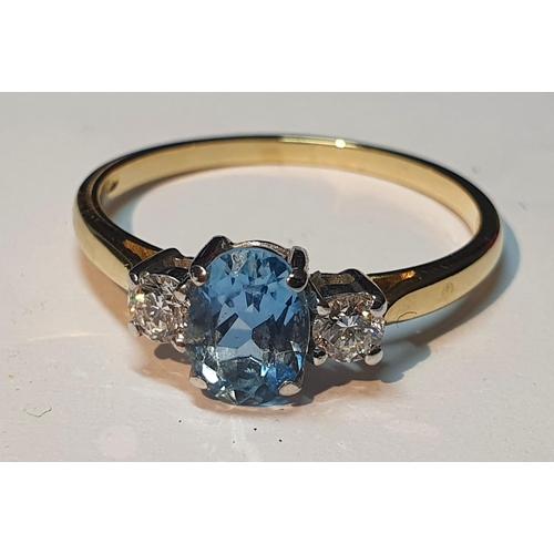 15 - An 18ct gold topaz and brilliant-cut diamond three-stone ring.