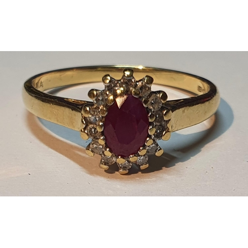 18 - An 18ct gold ruby and diamond cluster ring. Estimated total diamond weight 0.15ct. Hallmarks for 18c...