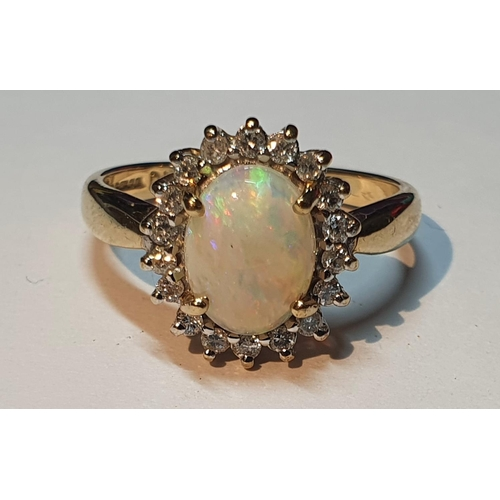 19 - A 9ct gold opal and brilliant-cut diamond cluster ring. Estimated total diamond weight 0.20ct. Hallm...