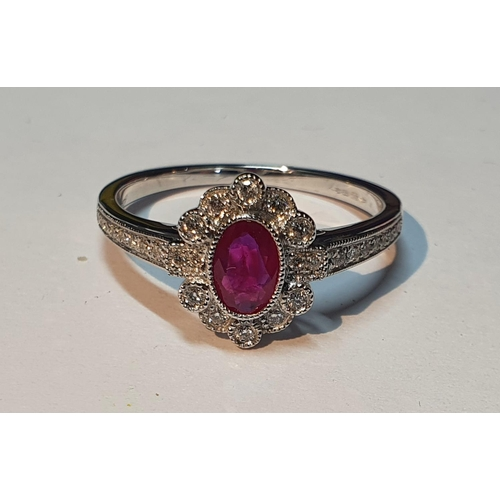 21 - An 18ct gold ruby and diamond cluster ring. Ruby weight 0.41ct. Total diamond weight 0.16ct. Hallmar...