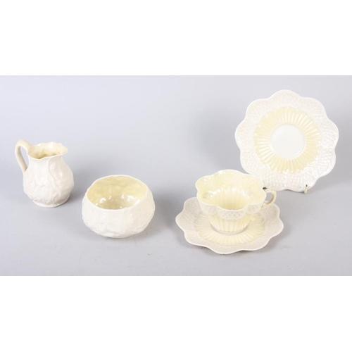 6 - A white glazed Belleek teacup, two saucers, a cream jug and a sugar bowl COLLECT...