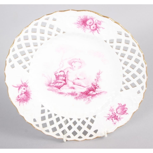 17 - A pair of bone china plates with puce cherub and floral decoration with pierced borders, 9 1/2