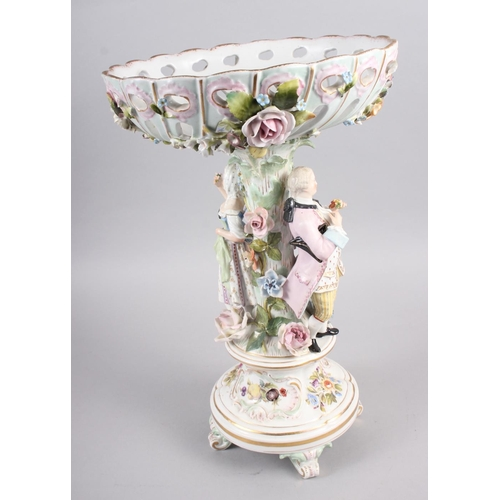 28 - A Continental porcelain table centre, the stem decorated with two figures and floral decoration to t...