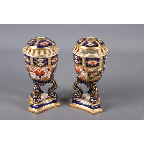 12 - A pair of Davenport Imari decorated pot-pourri vases and covers (one repaired with losses), on dolph...