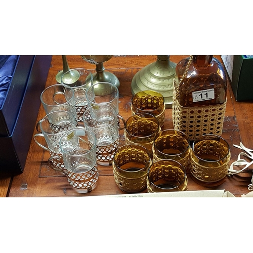 11 - A 1940s or '50s travel set: a darkened glass square bottle with six glasses with woven bamboo decora...